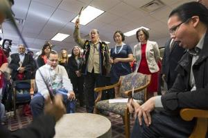 Clyde Bellecourt holds up a condor feather after leading a prayer before the Minneapolis City Council unanimously voted Friday, April 25, 2014, to recognize Columbus Day as Indigenous Peoples Day.