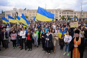 Ukrainians pray during a rally for a united Ukraine in Kharkiv, Ukraine, Wednesday, April 23, 2014. Poster at right reads, Putin stop.