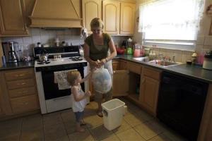 Amy Herendeen handing kitchen trash to her daughter Kaitlynn.