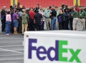 A Cobb County police officer speaks to FedEx employees and family members in Kennesaw, Ga.