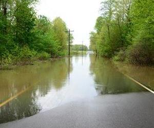 Waters stands across Bonds Road in McCracken County, which is closed at the intersection of Oaks Road due to flooding, Monday, April 28, 2014, in Paducah, Ky.
