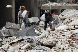 This photo, via anti-government activist group Aleppo Media Center, shows people carrying their belongings from a building hit by a Syrian government airstrike in Aleppo, Monday, April 28, 2014.