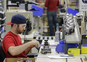 In this April 15, 2014 photo, a man wires blender motors at a facility in Strongsville, Ohio. The GDP's growth rate slowed to 0.1% in the first quarter.