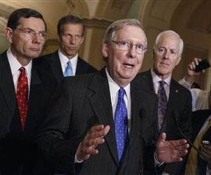 Senate Minority Leader Mitch McConnell of Ky., surrounded by GOP lawmakers, talks to reporters after a GOP caucus meeting, April 29, 2014, on Capitol Hill.