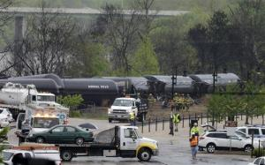 Firefighters work along the tracks where several CSX tanker cars carrying crude oil derailed in downtown Lynchburg, Va..