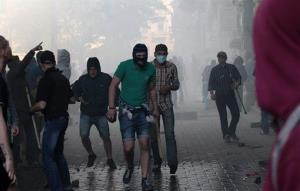 A Ukrainian government supporter (in green) holds a stone and a stick during a clash with pro-Russians in the Black Sea port of Odessa, Ukraine, Friday.