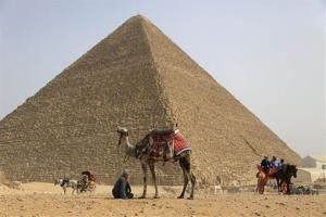 Tourists ride horses as a tour guide with camel waits for visitors at the Giza Pyramids in Giza, near Cairo, Egypt.