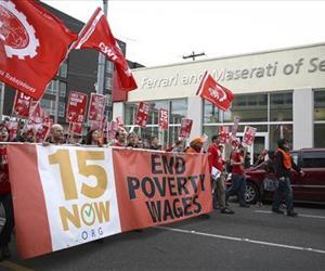 In this March 15, 2014, file photo people march during a rally to raise the minimum wage to $15 per hour in Seattle.