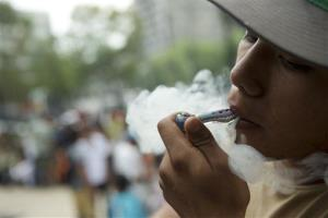 A young man smokes a pipe at a rally calling for the legalization of marijuana, in Mexico City, Saturday, May 3, 2014.