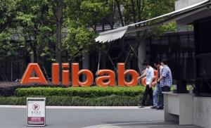 Men walk past the corporate logo at the headquarters of Alibaba Group in Hangzhou in eastern China's Zhejiang province.