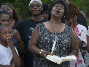 Hazel Embra holds a Bible while singing with others during a vigil for 93-year-old Pearlie Golden yesterday.