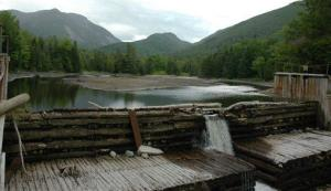 In this file photo, water flows over the damaged Marcy Dam in the Adirondacks in Lake Placid, N.Y.