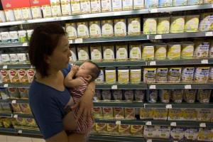 A woman carries a child past powdered milk products including cans of Dumex infant formula already inspected and deemed to be from a safe batch at a supermarket in Beijing, China, Aug. 5, 2013.