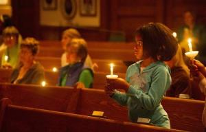 Karilyn Coates, 10, joins others in a candlelight vigil for the more than 300 girls abducted by Boko Haram in Nigeria, at All Souls Unitarian Church in Colorado Springs, Colo., Thursday, May 8, 2014.