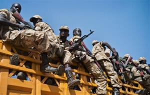 Some of hundreds of government soldiers board trucks, as they prepare to travel for the frontline near the town of Bor from the outskirts of Juba, South Sudan, Monday, Jan. 13, 2014.