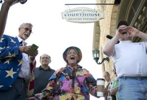 Sheila McFadden, center, and Ken Riley, right, yell words of encouragement at the crowd gathered in front of the Carroll County Courthouse in Eureka Springs, Ark., May 10, 2014.