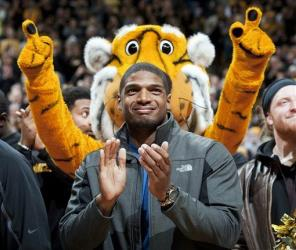 In this Feb. 15, 2014, photo, Missouri's All-American defensive end Michael Sam claps during the Cotton Bowl trophy presentation at halftime of an NCAA college basketball game.
