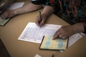 A polling station voluntary worker checks the passport of a voter at a polling station in the district of Budennovskiy, outskirts of Donetsk, Ukraine, Sunday, May 11, 2014.