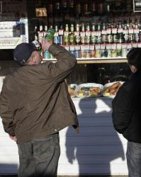 A Russian man drinks from a bottle standing in front of a liquor booth in a street in Moscow, Tuesday, March 23, 2010.