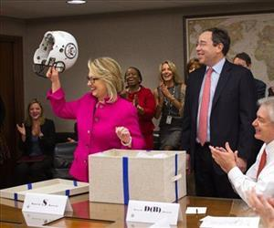 Secretary of State Hillary Rodham Clinton holds a football helmet presented to her at the State Department in Washington, Monday, Jan. 7, 2013, as she returned to work.