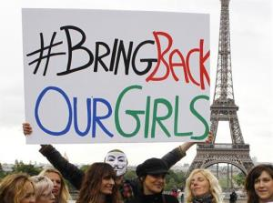 A person holds a poster during a rally in Paris for the Nigerian girls.