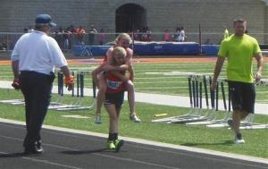 This May 10 photo provided by Ted Crail shows Claire Gruenke carrying her twin sister, Chloe, to the finish line.