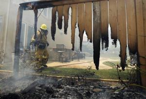 A firefighter puts water on a house fence during a wildfire  in Carlsbad, Calif.