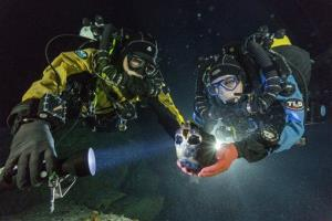 In this photo provided by National Geographic, divers Alberto Nava and Susan Bird transport the ancient skull to an underwater turntable so that it can be photographed.