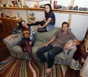 Lara Russo, left, Cally Guasti, center, and Reese Werkhoven sit on the Salvation Army sofa in their apartment in New Paltz, NY.