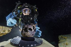 Diver Susan Bird, working at the bottom of a Mexican cave called Hoyo Negro, brushes an ancient human skull.