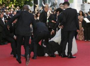Security officials pull away the man who dove under America Ferrara's dress.