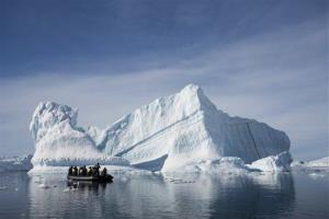 In this Dec. 1, 2009 file photo provided by Aurora Expeditions, an inflatable boat carries tourists past an iceberg along the Antarctic Peninsula.