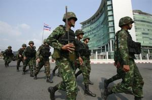 Thailand army soldiers arrive for security as pro-government supporters arrive outside the gate of the National Anti-Corruption Commission office in Bangkok, Thailand, Thursday, Feb. 27, 2014.