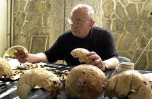 In a Friday June 2, 2000 file photo, forensic anthropologist Dr. Clyde Snow, of Oklahoma, unites parts of a skull, in San Salvador, El Salvador.