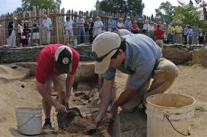 Michael Lavin, left, and Carter Hudgins, right, work together to remove layers of dirt from the site of the first permanent English settlement in Jamestown, Va.