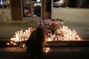 A woman places a candle in front of IV Deli Mart, where par of Friday night's mass shooting took place by a drive-by shooter, on Saturday, May 24, 2014.