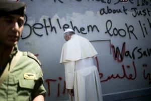Pope Francis prays at Israel's separation barrier on his way to a mass in Manger Square in the West Bank town of Bethlehem, Sunday, May 25, 2014.