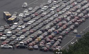 In this photo taken Monday, April 25, 2011, cars clog a main road in Beijing, China. China plans to take 6 million older, polluting vehicles off the road this year to clean up smog-choked cities.