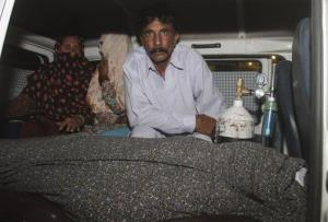 Mohammad Iqbal, right, husband of Farzana Parveen, 25, sits in an ambulance next to her body in Lahore.