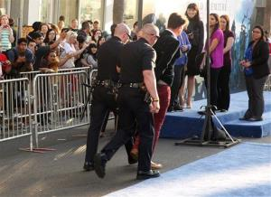 A man is walked off in handcuffs after allegedly attacking Brad Pitt at the premiere of Maleficent at the El Capitan Theatre on Wednesday, May 28, 2014, in Los Angeles.