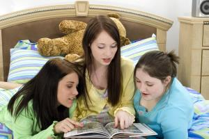 Girls look at a yearbook in this stock photo.