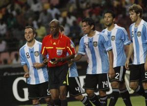 FILE -  In this Wednesday, June 1, 2011 file photo,  referee Ibrahim Chaibou, red top,  is surrounded by Argentina soccer players after he awarded a penalty against them during an international friendly soccer match with Nigeria Super eagles at the National stadium in  Abuja, Nigeria. It was in the final...