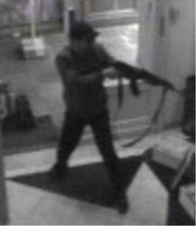 In this file photo distributed on Sunday, May 25, 2014, a surveillance camera shows a man shooting at the Jewish museum in Brussels, Belgium, on Saturday, May 24, 2014.