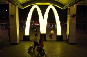 Passengers walk near a large sign for a McDonald's at a train station in northern China.