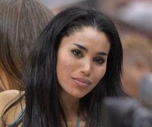 In this photo taken on Friday, Oct. 25, 2013, V. Stiviano, left, watches the Clippers play the Sacramento Kings during the first half of an NBA basketball game in Los Angeles.