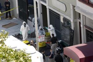 Agents in hazardous material suits are seen as the FBI searches a building in San Francisco on Saturday.