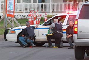 Police officers take cover behind their vehicles in Moncton, New Brunswick.