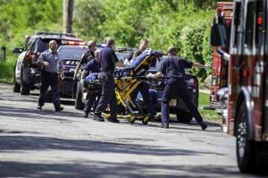 Rescue workers take a stabbing victim to the ambulance in Waukesha, Wis., on Saturday.