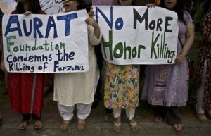 Members of Pakistan's civil society hold banners and chant slogans during a protest to condemn the killing of pregnant woman Farzana Parveen.
