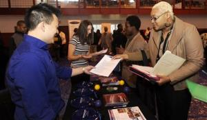 In this April 23, 2014 photo, Luke Gill, of Quicken Loans, left, talks with job candidate Jasmine Boykins at a job fair at the Matrix Center in Detroit.